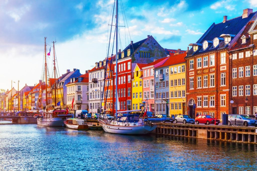 Copenhagen things to do-Scenic summer sunset view of Nyhavn pier with color buildings, ships, yachts and other boats in the Old Town of Copenhagen